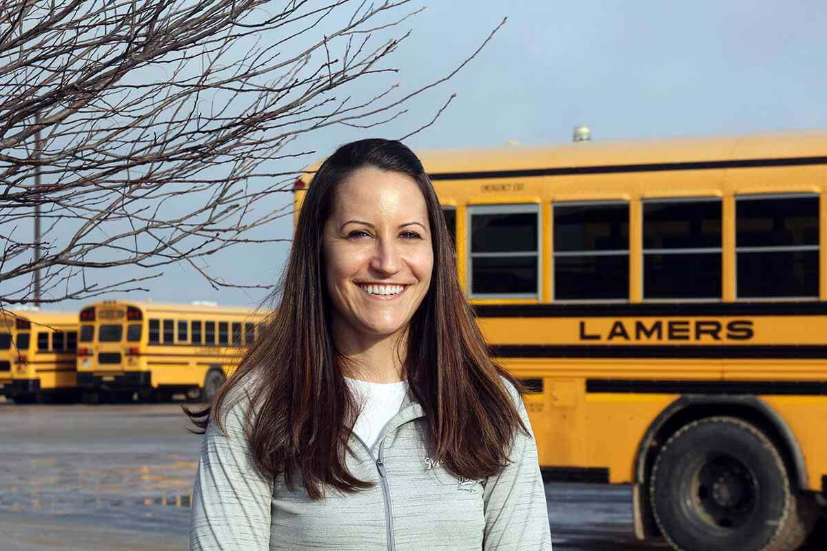 Lamers Bus Lines, Inc. employee in front of school bus